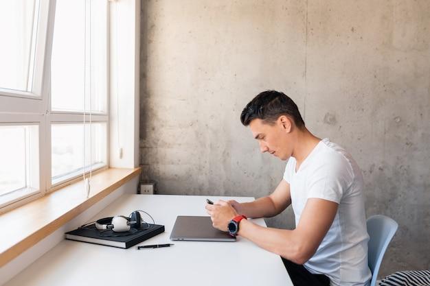 Jonge knappe lachende man in casual outfit zittend aan tafel bezig met laptop alleen thuis blijven, typen