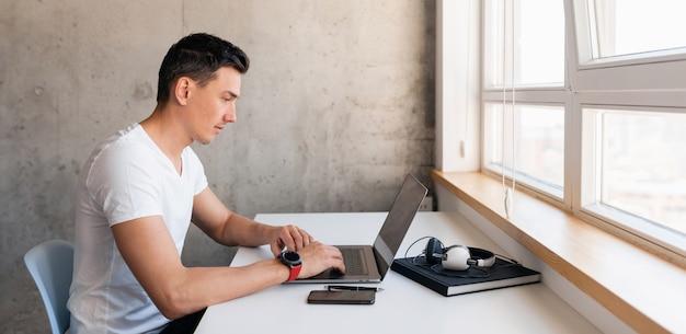 Jonge knappe lachende man in casual outfit zittend aan tafel bezig met laptop alleen thuis blijven