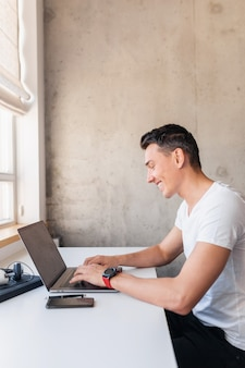 Jonge knappe lachende man in casual outfit zittend aan tafel die op laptop werkt