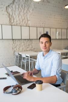 Jonge knappe lachende man zit in open ruimte kantoor die op laptop werkt