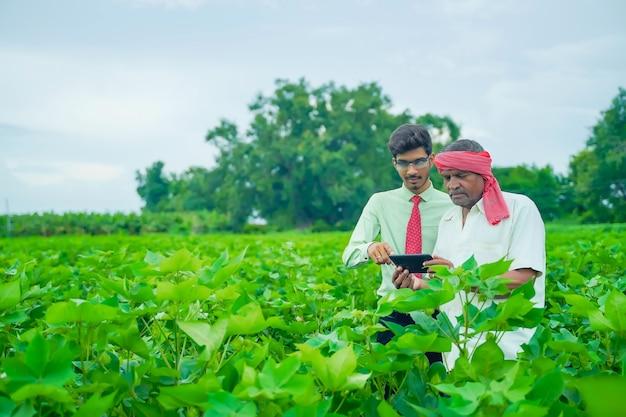 Jonge knappe landbouwingenieur en landbouwer die katoengebied met tablet inspecteert