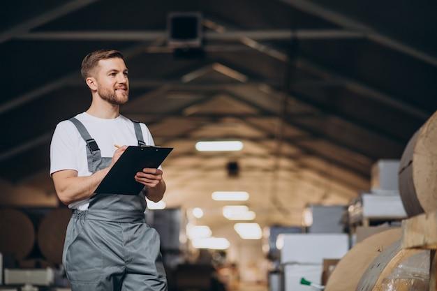 Jonge knappe man aan het werk in een fabriek