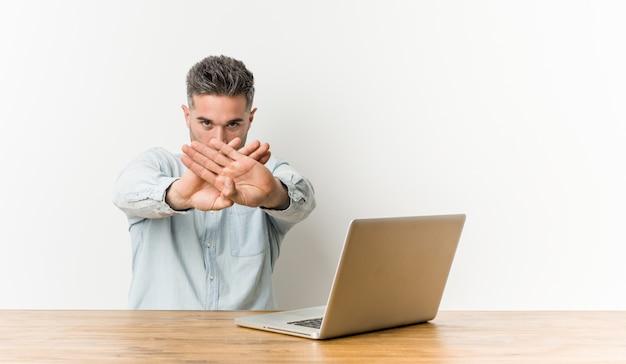Jonge knappe man aan het werk met zijn laptop doet een ontkenningsgebaar