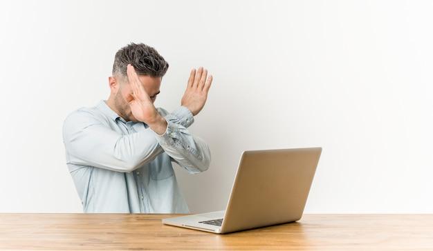 Jonge knappe man aan het werk met zijn laptop houden twee armen gekruist