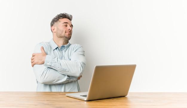 Jonge knappe man aan het werk met zijn laptop knuffels, glimlachend zorgeloos en gelukkig.