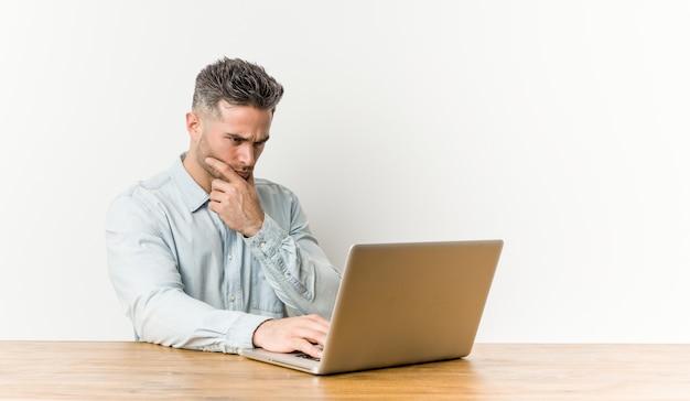 Jonge knappe man aan het werk met zijn laptop opzij met twijfelachtige en sceptische uitdrukking.