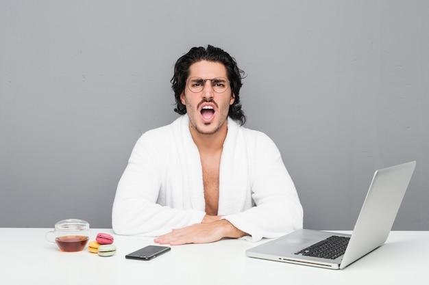 Jonge knappe man aan het werk na een douche, erg boos en agressief gillend.
