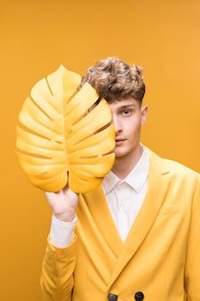 Jonge knappe man achter palmblad in een gele scène