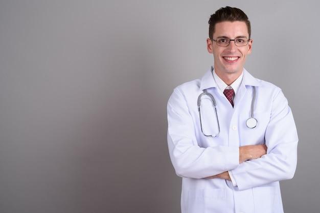 Jonge knappe man arts bril dragen op grijs