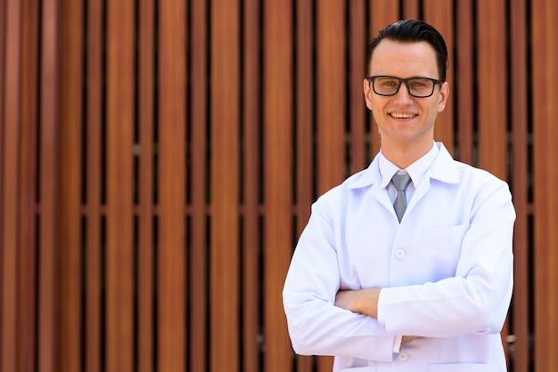 Jonge knappe man arts met bril buitenshuis