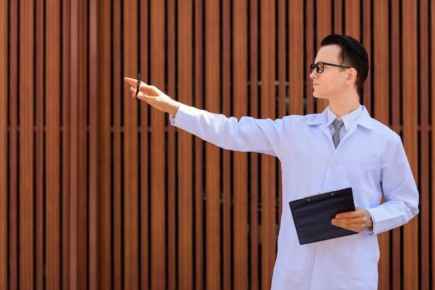 Jonge knappe man arts met bril klembord buitenshuis te houden