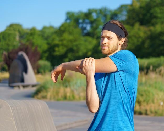 Jonge knappe man atleet opwarmen voor ochtendtraining in groen park in