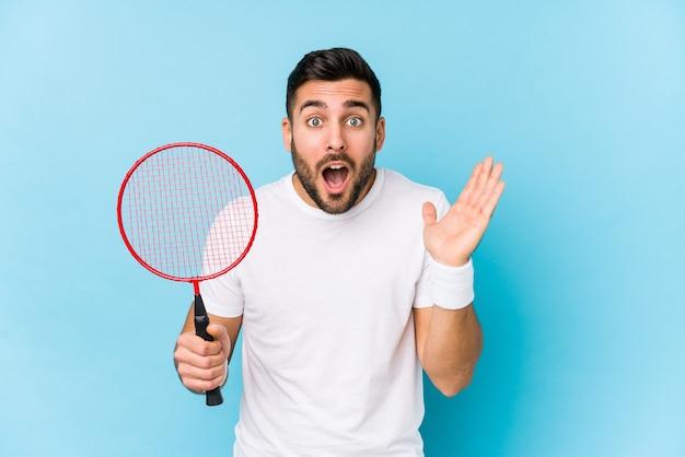 Jonge knappe man badminton spelen geïsoleerd verrast en geschokt.