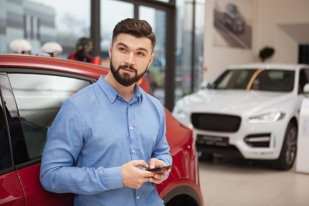 Jonge knappe man bedachtzaam wegkijken tijdens het gebruik van slimme telefoon bij autodealer, kopieer ruimte