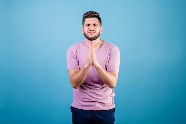 Jonge knappe man bidden hopen op geluk geïsoleerd op blauw
