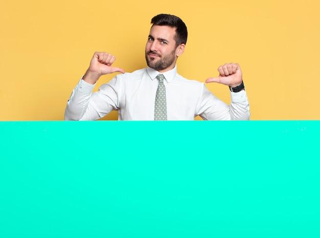Jonge knappe man blij en trots, wijzend naar zichzelf met groen bord
