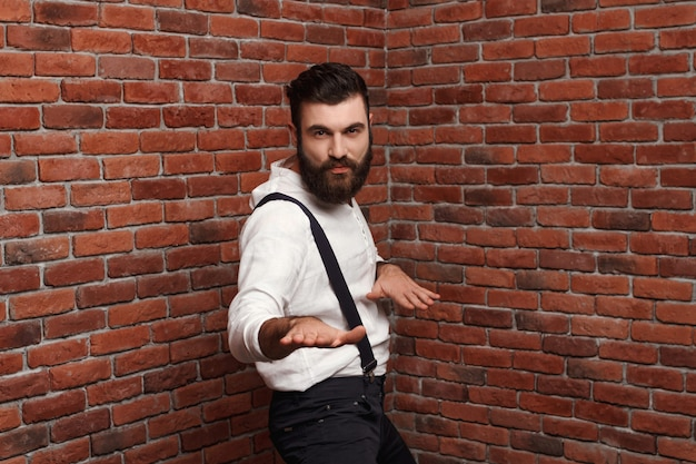 Jonge knappe man dansen poseren op bakstenen muur.
