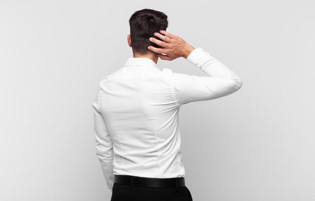 Jonge knappe man denken of twijfelen, hoofd krabben, zich verbaasd en verward voelen, achter- of achteraanzicht
