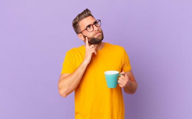 Jonge knappe man denkt, voelt zich twijfelachtig en verward. en een koffiemok vasthouden