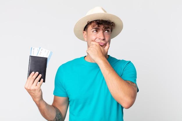 Jonge knappe man denkt, voelt zich twijfelachtig en verward. reiziger met zijn paspoort