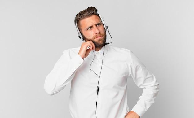 Jonge knappe man denkt, voelt zich twijfelachtig en verward. telemarketing concept