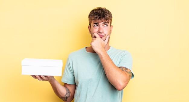 Jonge knappe man denkt, voelt zich twijfelachtig en verward. witte doos concept