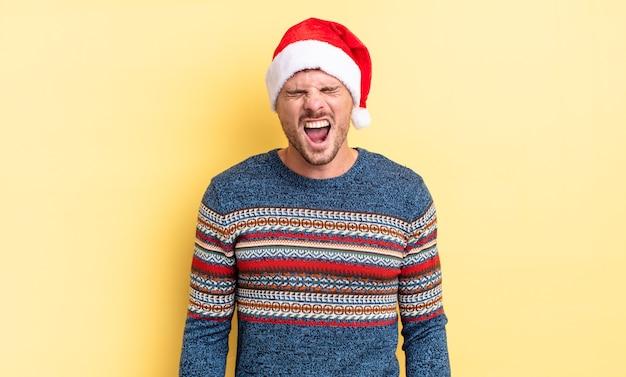Jonge knappe man die agressief schreeuwt en er erg boos uitziet. kerst concept