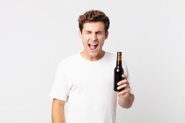 Jonge knappe man die agressief schreeuwt, erg boos kijkt en een bierfles vasthoudt