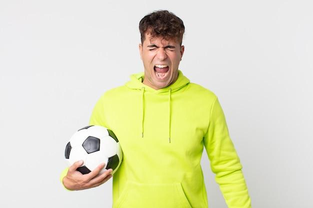 Jonge knappe man die agressief schreeuwt, erg boos kijkt en een voetbal vasthoudt