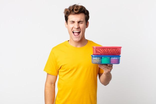 Jonge knappe man die agressief schreeuwt, erg boos kijkt en lunchboxen vasthoudt
