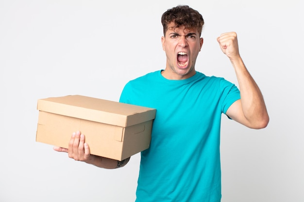 Jonge knappe man die agressief schreeuwt met een boze uitdrukking en een kartonnen doos vasthoudt