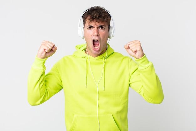 Jonge knappe man die agressief schreeuwt met een boze uitdrukking en koptelefoon