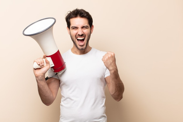 Jonge knappe man die agressief schreeuwt met een boze uitdrukking of met gebalde vuisten om succes te vieren