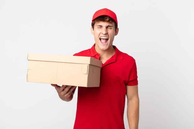 Jonge knappe man die agressief schreeuwt, op zoek naar een erg boos leveringspakketserviceconcept.