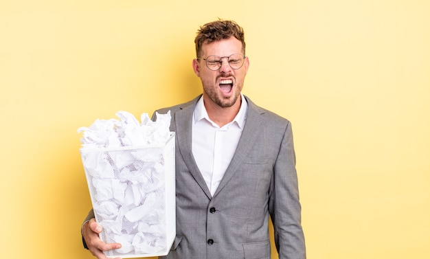 Jonge knappe man die agressief schreeuwt, op zoek naar een heel boos afvalconcept met papieren ballen