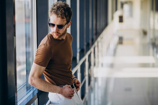 Jonge knappe man die bij het raam op de luchthaven