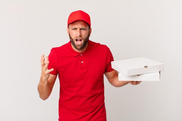 Jonge knappe man die boos, geïrriteerd en gefrustreerd kijkt. pizza bezorgconcept