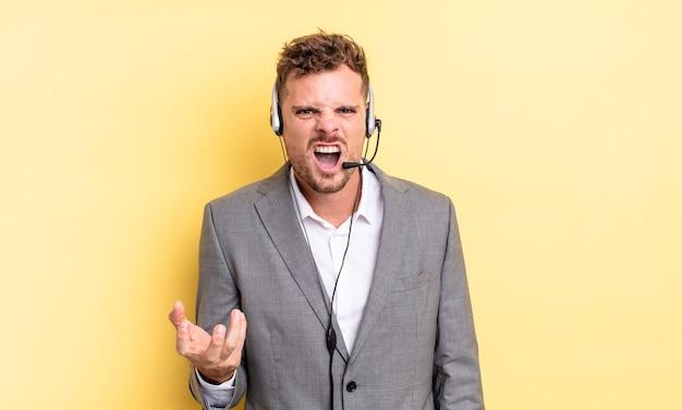 Jonge knappe man die boos, geïrriteerd en gefrustreerd kijkt. telemarketeer concept