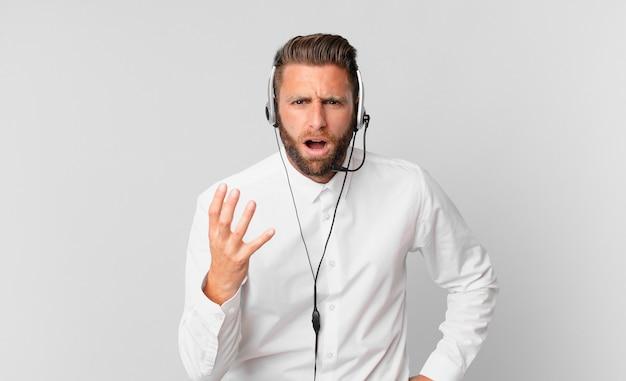Jonge knappe man die boos, geïrriteerd en gefrustreerd kijkt. telemarketing concept