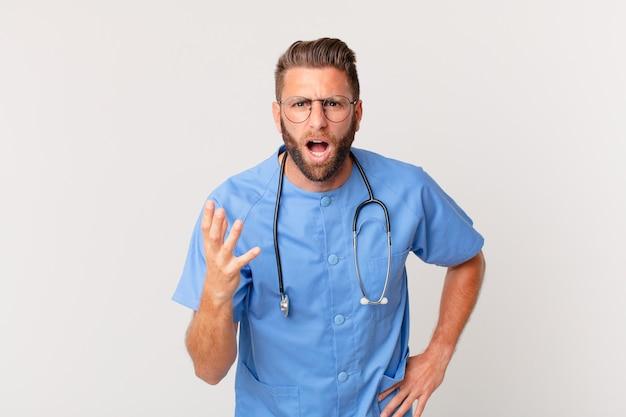 Jonge knappe man die boos, geïrriteerd en gefrustreerd kijkt. verpleegster concept