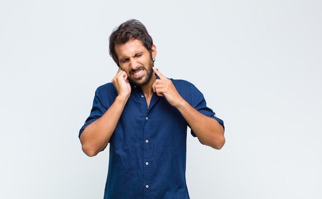 Jonge knappe man die boos, gestrest en geïrriteerd kijkt, beide oren bedekt met een oorverdovend geluid, geluid of luide muziek