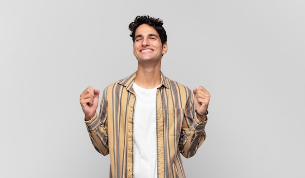 Jonge knappe man die buitengewoon blij en verrast kijkt, succes viert, schreeuwt en springt