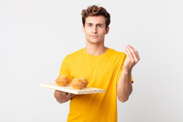 Jonge knappe man die capice of geldgebaar maakt en je vertelt dat je moet betalen met een dienblad met muffins