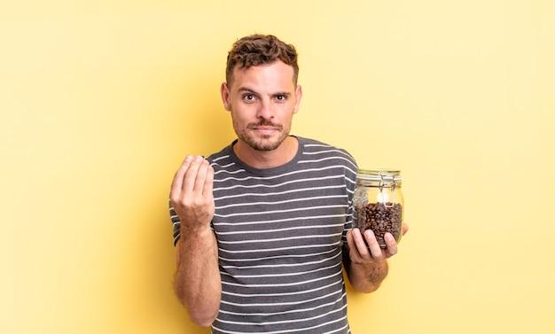Jonge knappe man die capice of geldgebaar maakt en je vertelt om het concept van koffiebonen te betalen