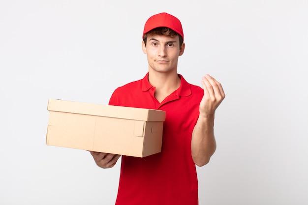 Jonge knappe man die capice of geldgebaar maakt en u vertelt dat u het serviceconcept voor het leveringspakket moet betalen.