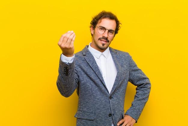 Jonge knappe man die capice of geldgebaar maakt en zegt dat je je schulden moet betalen! op oranje muur