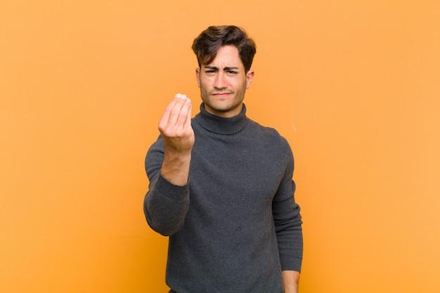 Jonge knappe man die capice of geldgebaar maakt en zegt dat je je schulden moet betalen! tegen oranje muur