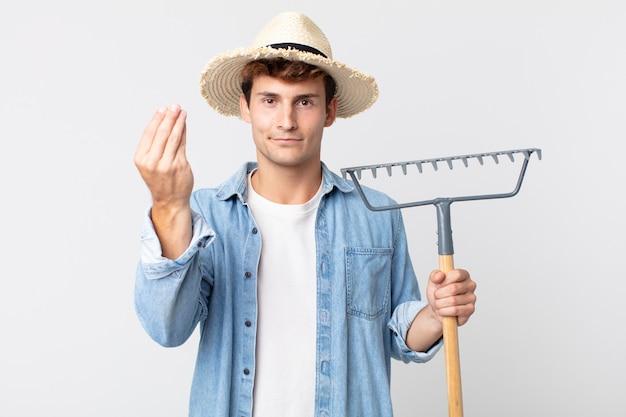 Jonge knappe man die capice of geldgebaar maakt en zegt dat je moet betalen. boer concept