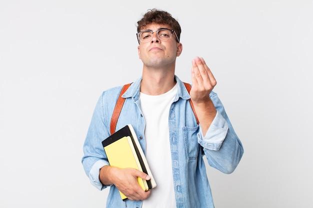 Jonge knappe man die capice of geldgebaar maakt en zegt dat je moet betalen. universitair studentenconcept