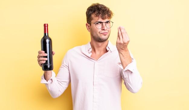 Jonge knappe man die capice of geldgebaar maakt en zegt dat je moet betalen. wijnfles concept